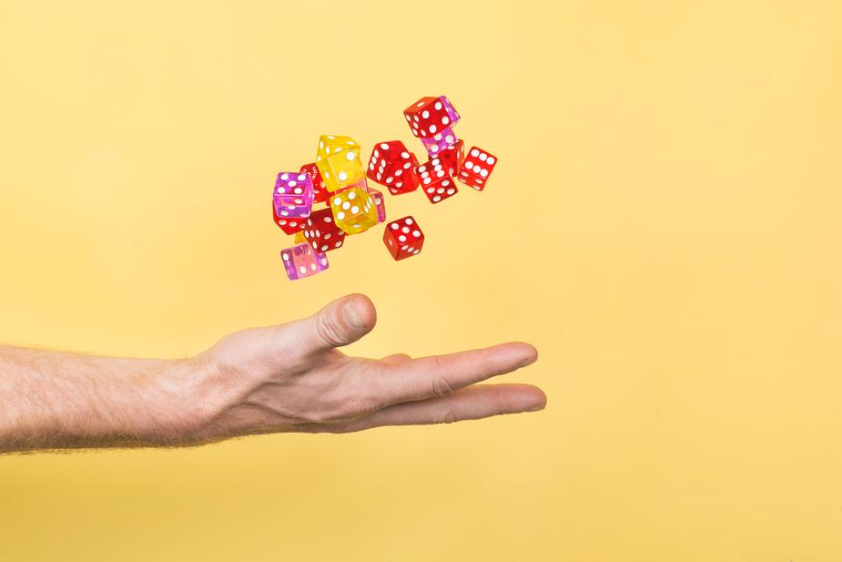 hand-throwing-dice-on-yellow_925x